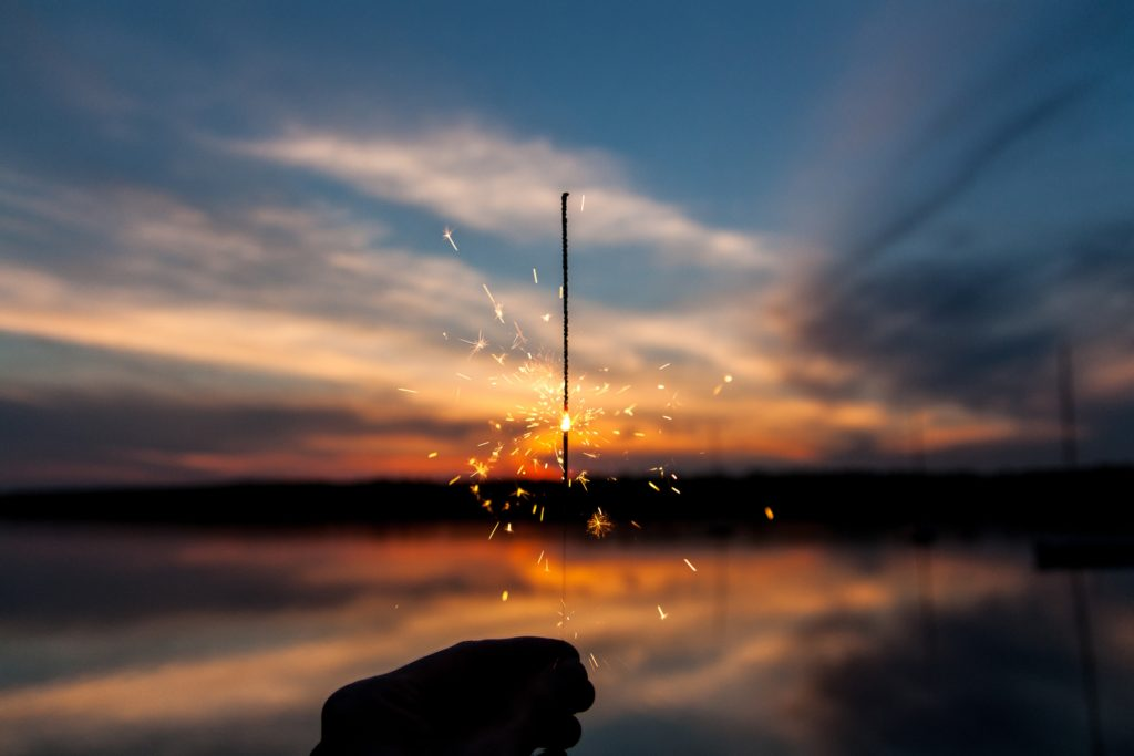 Hand holding a sparkler with a sunset in the background.