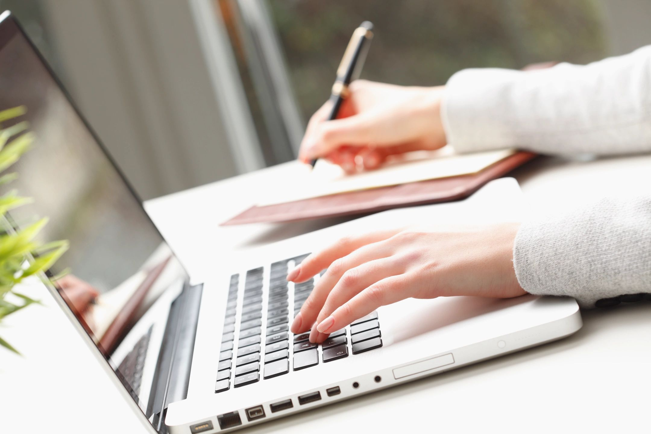 Hands typing and writing
